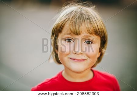 Outdoor close up portrait of adorable 6 year old kid boy candid facial expression