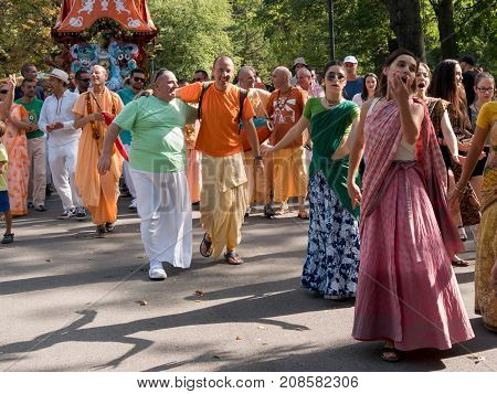 SOFIA,BULGARIA - SEPTEMBER 17, 2017: The cart festival called 'Ratha Yatra' in Sofia . Priests throw fruits offered to the deities, to the people lifting up their hands to catch