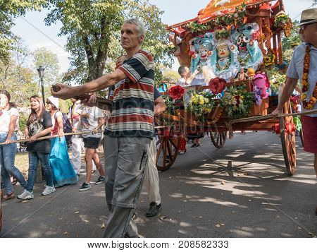 SOFIA,BULGARIA - SEPTEMBER 17, 2017: The cart festival called 'Ratha Yatra' in Sofia . Priests throw fruits offered to the deities, to the people lifting up their hands to catch.