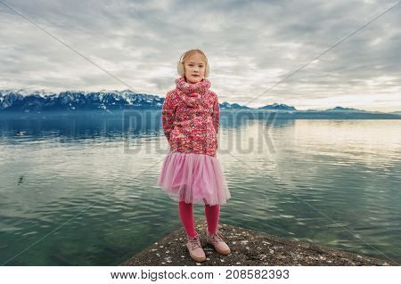 Adorable little girl resting by lake Geneva on a cold winter day wearing warm pink pullover tutu skirt tights and shoes image taken in Lausanne Switzerland