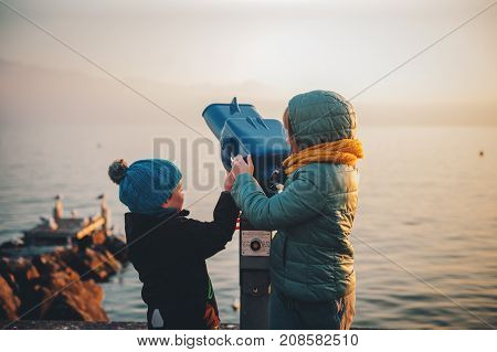 Little kids looking at coin operated binocular by Geneva lake in wintertime