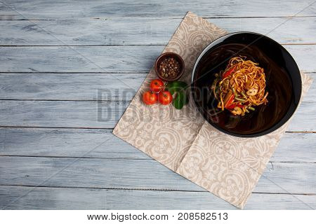 Traditional Chinese dish on a round black plate, rice noodles, cabbage green cabbage and fried vegetables, red cherry tomatoes. On a wooden gray table. Close-up. View from above.