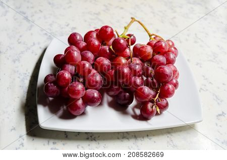 A Studio Photograph of a Bunch of 'Flame' Variety (Vitis Vinifera) Grapes on a Serving Plate