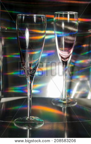 A Studio Photograph of Two Champagne Flutes Set Against a Silver Holographic Backdrop