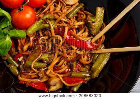 Traditional Chinese dish on a round black plate, rice noodles, cabbage green cabbage and fried vegetables, red cherry tomatoes. Chinese chopsticks. On a wooden gray table. Close-up. View from above.