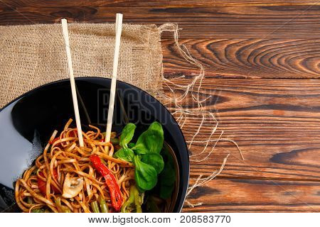 Traditional Chinese dish on a round black plate, rice noodles, cabbage or green cabbage and fried vegetables. Chinese chopsticks. On a wooden brown table. Close-up. View from above.