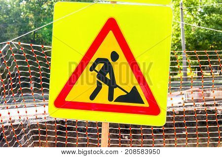Road sign at the construction site in summer day