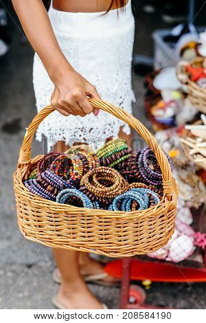 Native handcrafts colorful bracelets in the basket. Woman hand carrying basket with full of hand made bracelets