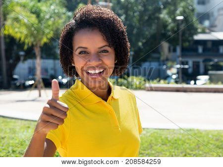 Joyful laughing african american woman showing thumb up outdoor in the city