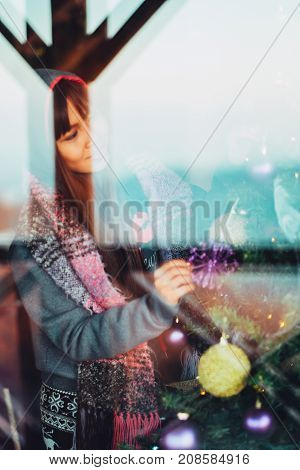 Young beautiful Asian woman in winter coat decorating Christmas tree at home.Young woman portrait shot trough the window. Selective Focus