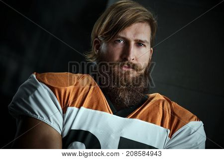 Portrait of bearded american football player looking at camera with dedication.