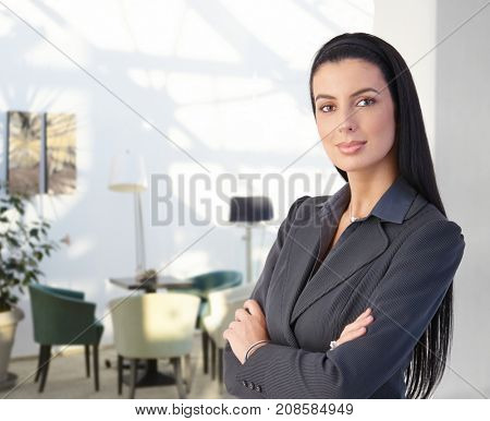 Smartly dressed smiling businesswoman at office standing arms crossed.