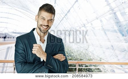 Happy young businessman smiling at camera in office lobby with copyspace.