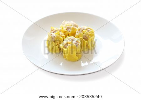 yellow skin dimsum shumai dumpling on a white plate