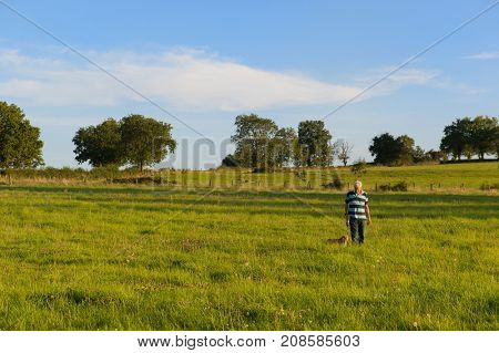 Man walking the dog in landscape with fields and trees