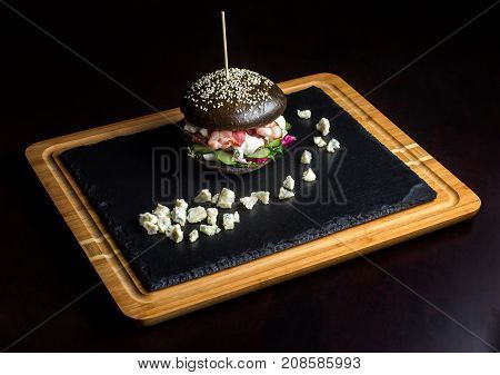 Black hamburger made from beef, with dor-blu. It lies on a black slate, before it is laid out cheese with blue mold.