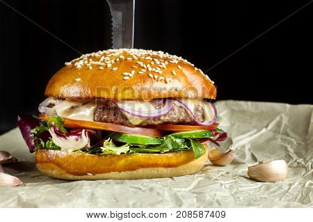 Hamburger with garlic is on kraft paper. Behind the black background.