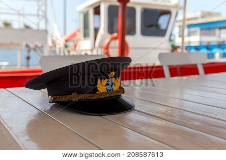 Black captain's cap with an anchor on the ship's desk.