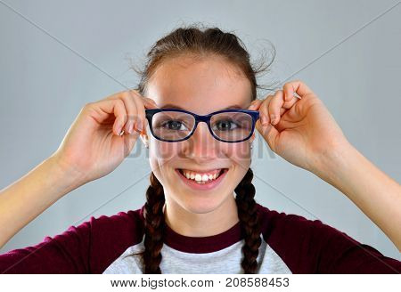 Cheerful pretty young woman with glasses on gray background.