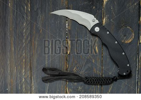 Knife In The Form Of A Sickle. Knife For Military Operations. Black Background.