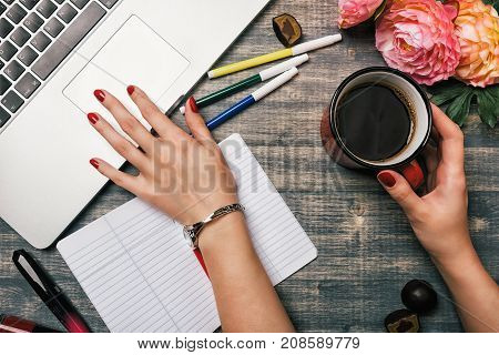 Office table desk, Flat lay. Workspace with flowers laptop red cup candy lipstick on wooden background. Woman hand writing in a notebook