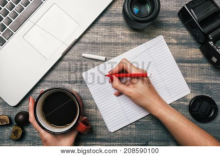 Office table desk, Flat lay. Workspace with laptop red cup candy lens and flash on wooden background. Woman hand writing in a notebook