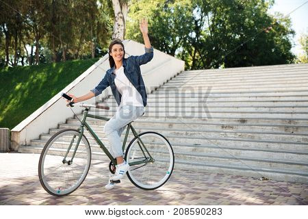 Portrait of a happy pretty girl waving hand while riding on a bicycle and looking away outdoors