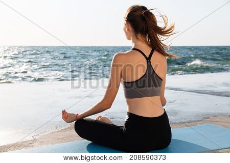 Portrait of young healthy woman sitting in lotos pose while practicing meditation at seaside
