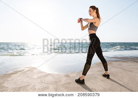 Full-length photo of young sport woman with perfect body checking time, seaside outdoor