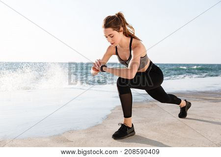 Portrait of young healthy sport woman checking time while doing fitness exercise for legs, seaside outdoor