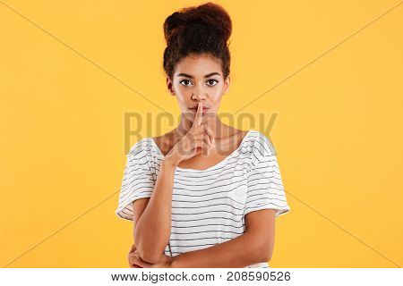 Portrait of serious calm confident woman showing silence gesture and looking camera isolated