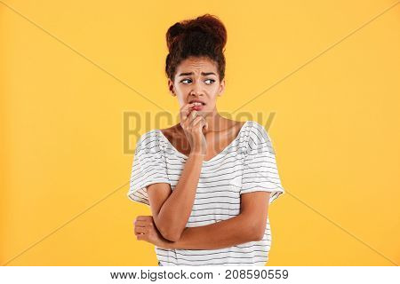 Young displeased afro-american woman looking aside with disgust isolated over yellow