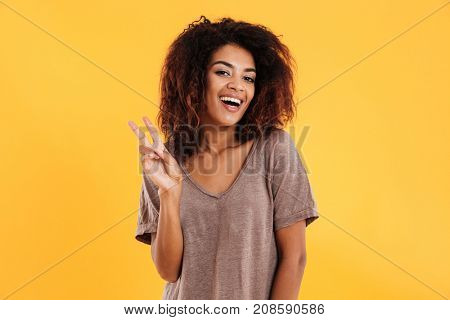 Cheerful african woman showing peace sign and looking at the camera over yellow background