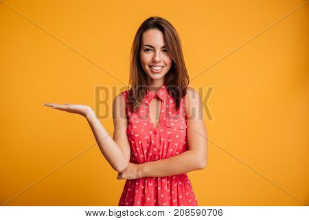 Smiling brunette woman in dress holding copyspace on the pound and looking at the camera over yellow background