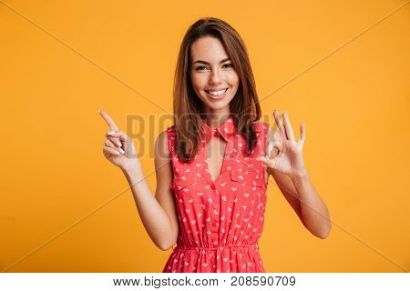 Smiling brunette woman in dress pointing up and showing ok sign while looking at the camera over yellow background