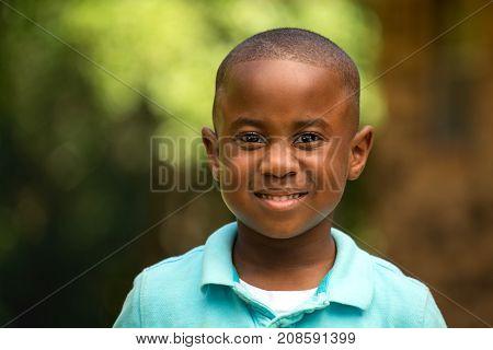 Cute African American little boy smiling outside.