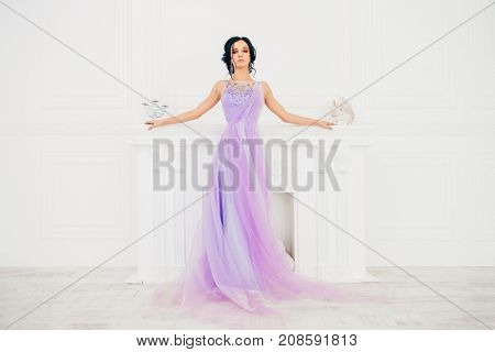 Full length portrait of a charming bride woman in a beautiful purple wedding dress. Luxurious apartments.