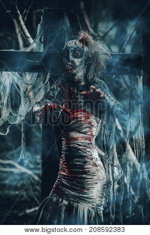 Dead bride woman on an abandoned cemetery. Zombie bride. Halloween.