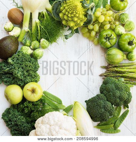 Above view of green vegetables and fruits arranged in a circle frame, copy space for text in the middle, square, selective focus
