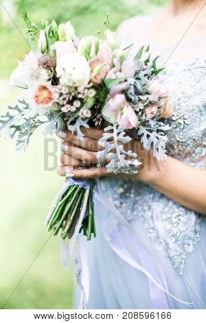 Bride holding wedding bouquet outdoors, daylight rustic style