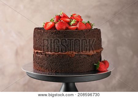 Delicious chocolate cake with strawberries on stand, closeup