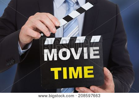 Businessperson Holding Clapboard With Text Movie Time
