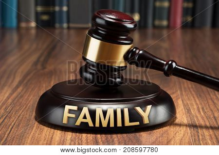 Close-up Of A Gavel With Family Text On Wooden Table
