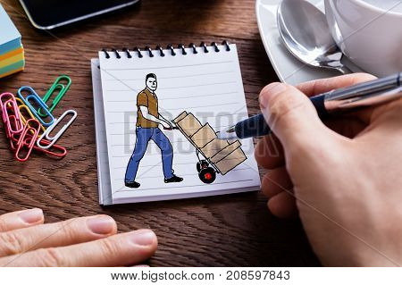 Close-up Of A Person's Hand Drawing Delivery Man Moving Trolley Full Of Boxes On Notepad