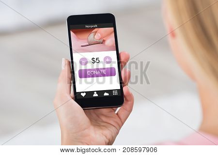 Close-up Of A Business Woman Holding Mobile Phone Donating Money Online