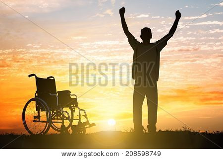 Silhouette Of Miracle Handicapped Man Walking Again At Sunset