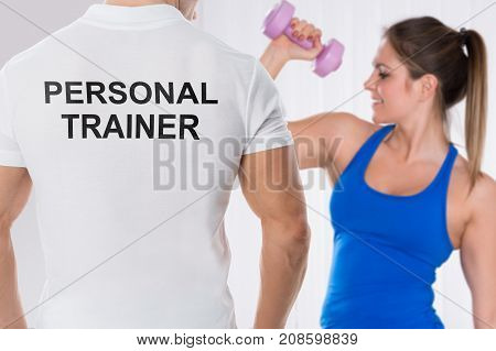 Young Woman Doing Exercise With Dumbbell In Front Of Personal Trainer