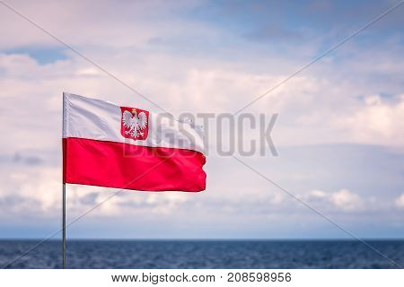 Red and white Polish flag with national eagle emblem fluttering in the wind on a seaside