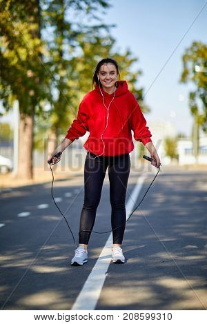 Young woman in red sweatshirt smiling jumping rope in park. Close-up . In full growth.