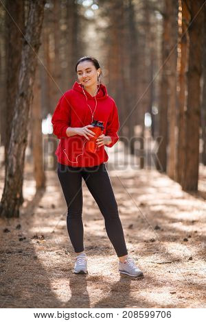 Young sporty woman in red sweatshirt and headphones. In the woods. Holds a red sport bottle. In full growth.